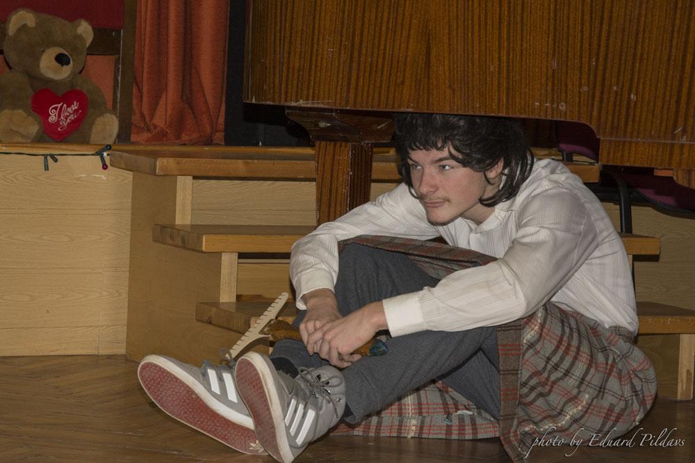 Ilmārs kādā lomā sēž uz grīdas skolas zālē.