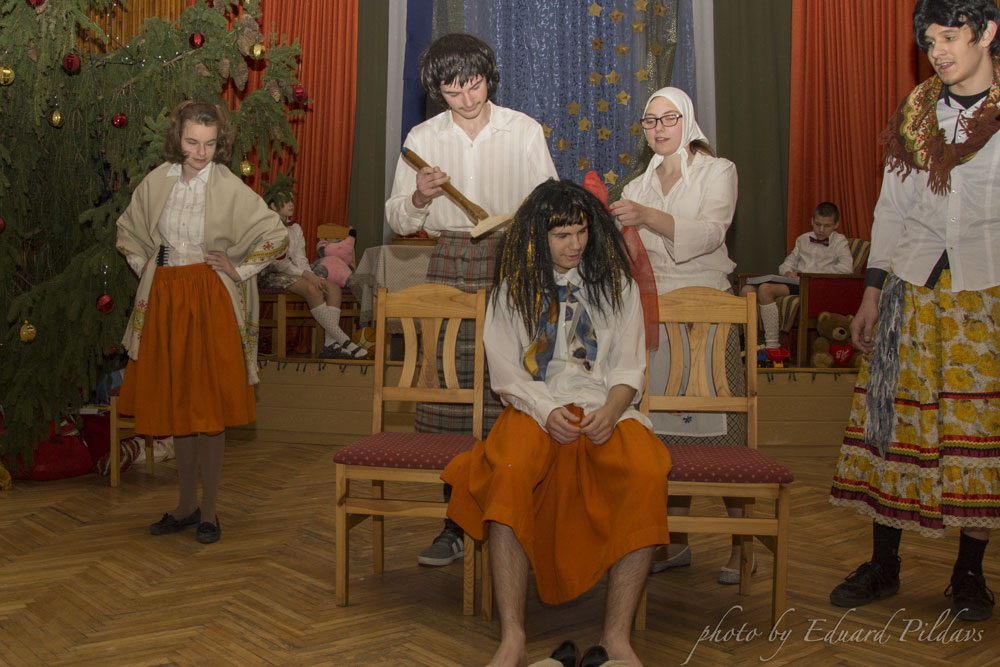 Griša, Ilmārs, Rihards, Alise, Aigija skolas zālē dīvainos apģērbos spēlē teātri.