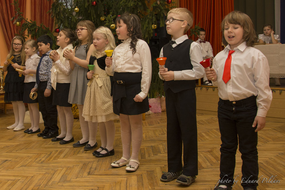 Jaunāko klašu bērni skolas zālē rindā dzied un spēlē zvaniņus.