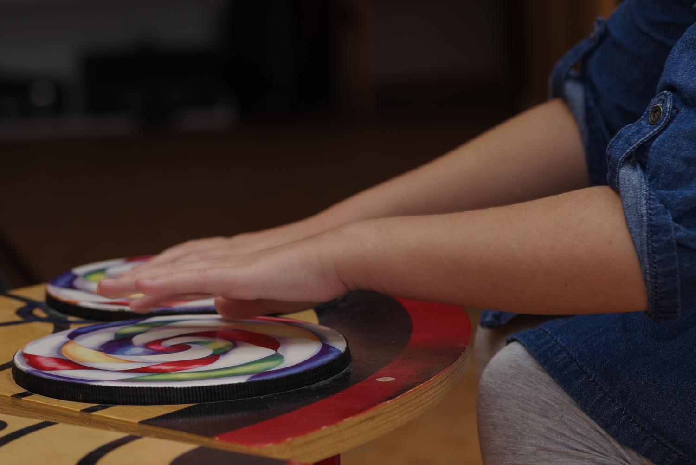 Bērna rokas virs sensoriem skaņu apļiem.