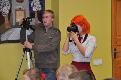 Artūrs un Sofija filmē un fotogrāfē kādu skolas pasākumu.