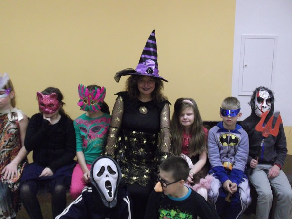 Skolotāja Ligita ar bērniem maskās sasēdušies rindā.