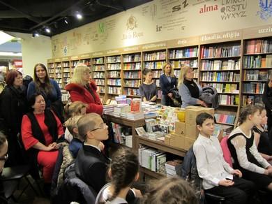 Bērni grāmatnīcā sēž un klausās stāstīto, vairāki pieaugušie stāv.