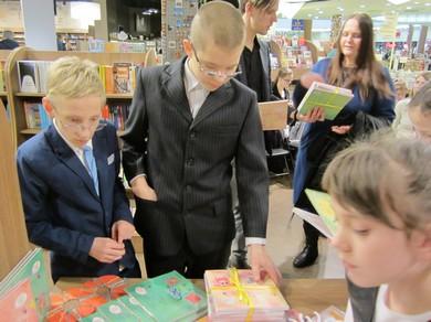 Skolēni pie galda skatās grāmatas, tālāk sieviete rāda grāmatas kādam vīrietim.