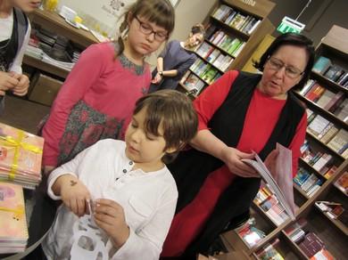 Skolotāja Baiba Pika ar diviem skolēniem pie grāmatu stenda.