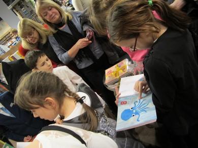 Bērni skatās un tausta grāmatu zīmējumus.