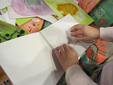 Bērna rokas braila grāmatā lasa tekstu.