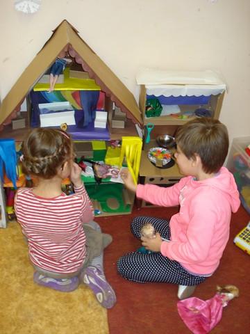 Bērni spēlējas pie uzdāvinātās rotaļu mājas.