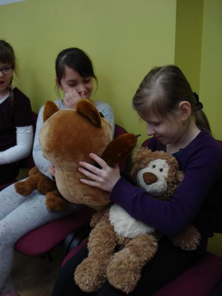 Meitenes sēž, rokās rotaļu lāči.