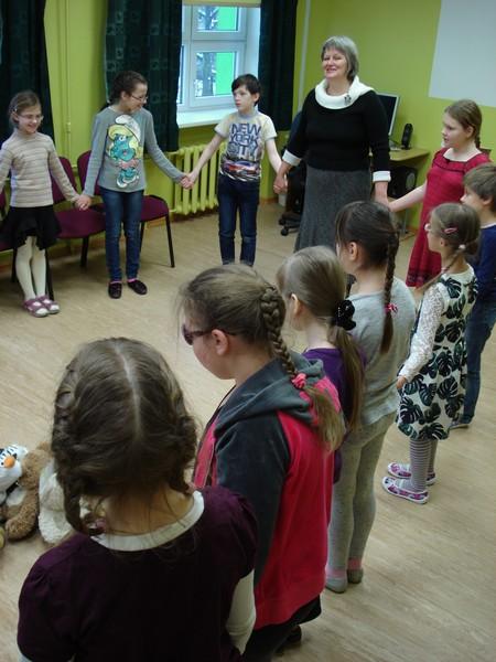 Bērni ar biblitekāri aplī, sadevušies rokās, apļa vidū kaudzē rotaļu lāči.