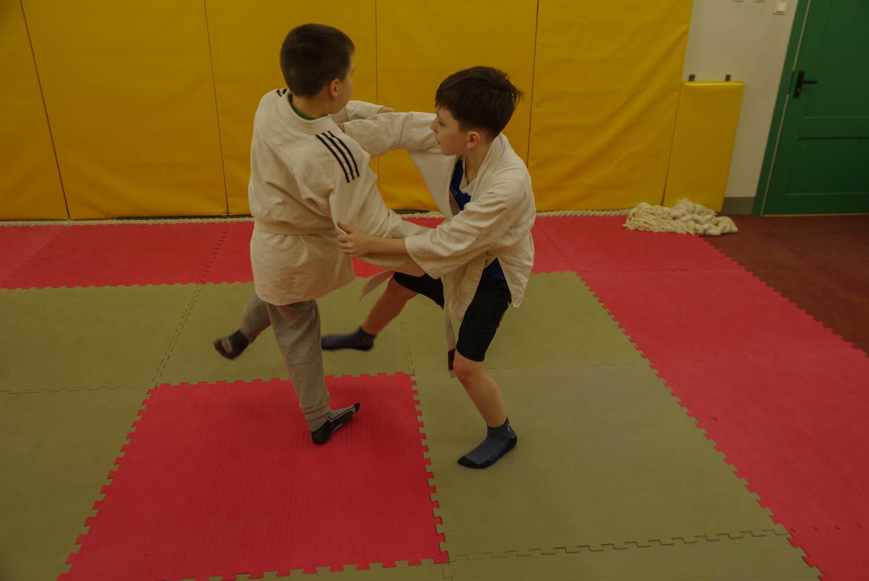 Divi zēni cīnās uz tatami.