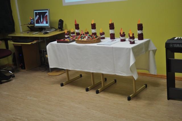 Svētku galds ar sarkanbaltsarkanām svecēm.