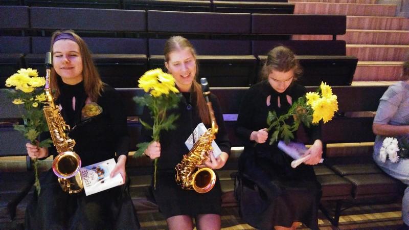 Visas trīs meitenes smaidīgas sēž ar uzdāvinātajiem ziediem