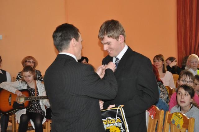 Skolotājs Vladimirs Priede piesprauž žetonu Nikolajam.