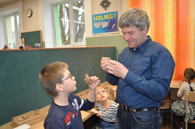 Meisters zēnam rāda kā veidot māla figūriņas