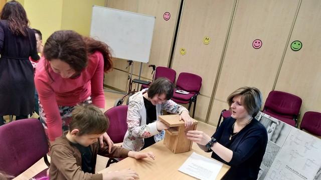 Skolotājas ar bērniem veido putnu būrīti.