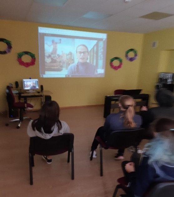 Skolēni konferenču zālē skatās tiešraidi.