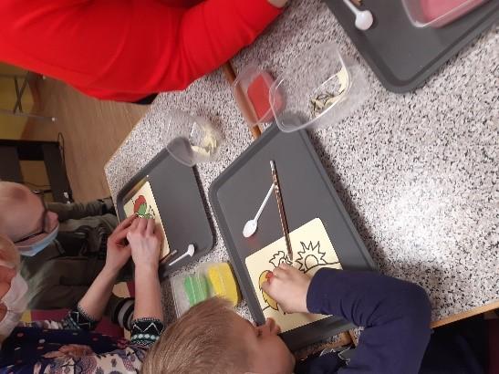 Divi bērni pie galda skolotājs vadībā zīmē.