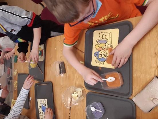 Skolēni ar smiltīm papildina savus zīmējumus.