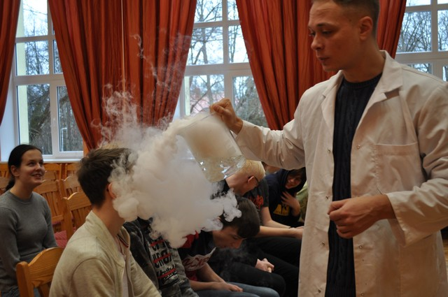 Izrādes vadītājs pirmajā rindā laiž virsū aukstos dūmus.
