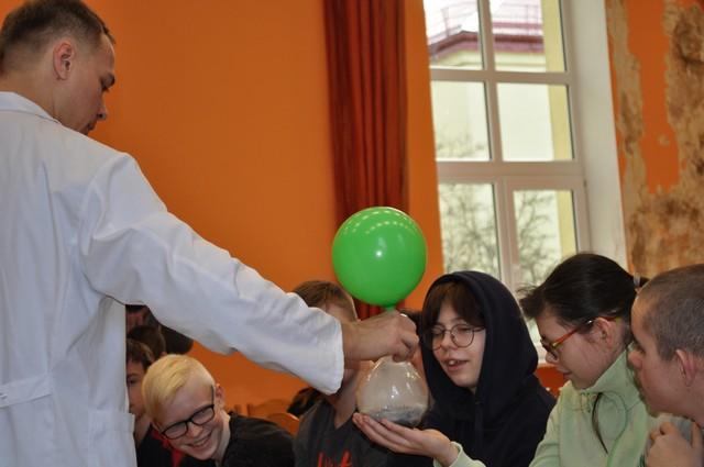 Izrādes vadītājs skolēniem demonstrē kā gāze uzpūš balonu.