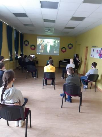 Skolēni Konferenču zālē ar 2 m distanci skatās un klausās koncertu.
