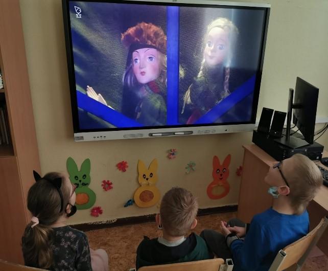 Trīs skolēni klasē uz inteaktīvā ekrāna skatās Sniega karalienes izrādi.