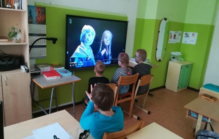 Četri skolēni skatās izrādi uz interaktīvā ekrāna. Trīs tuvu ekrānam, viens zēnes - tālāk.