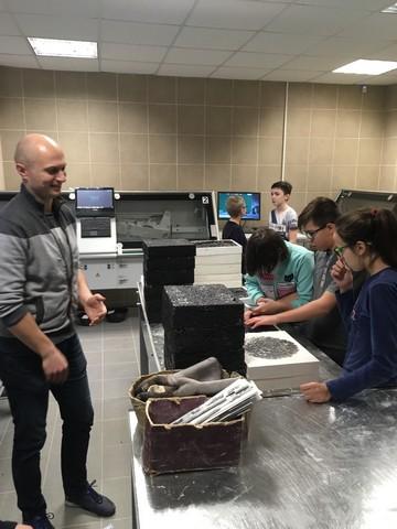 Bērni ar nodarbību vadītāju pie laboratorijas galdiem