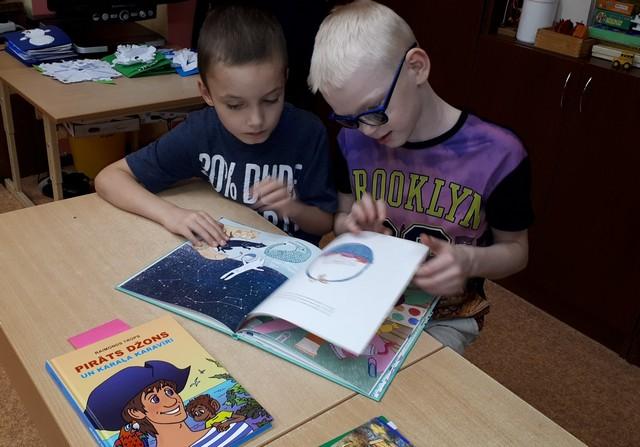 Divi zēni pāršķir lapas grāmatai