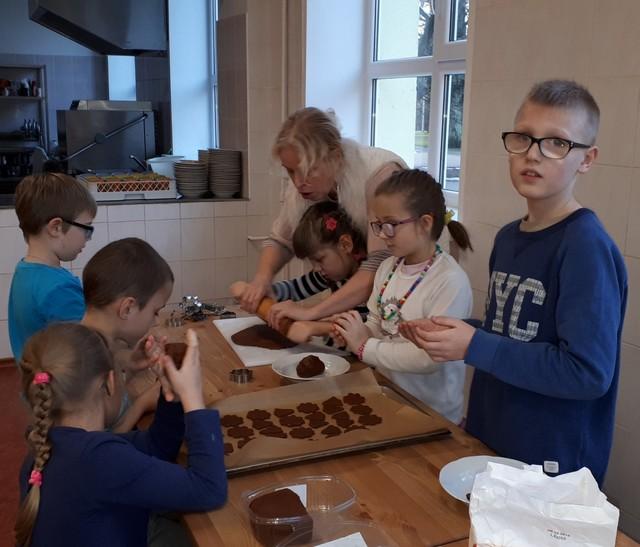 Bērni ar skolotāju pie galda rullē piparkūku mīklu