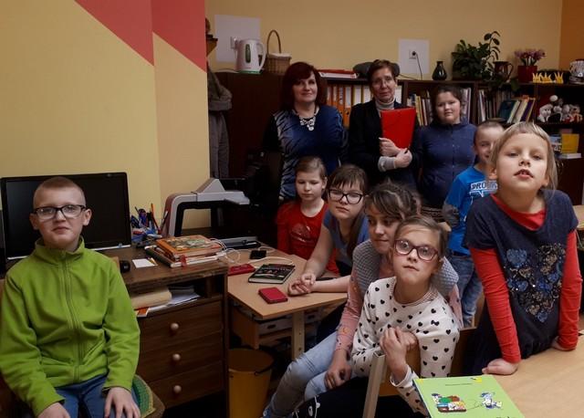 Skolēni ar skolotāju un bibliotekāri klasē
