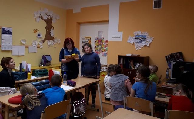 Skolotāja lasa priekšā grāmatu. Skolēni klausās. Viena meitene nostājusies blakus skolotājai.