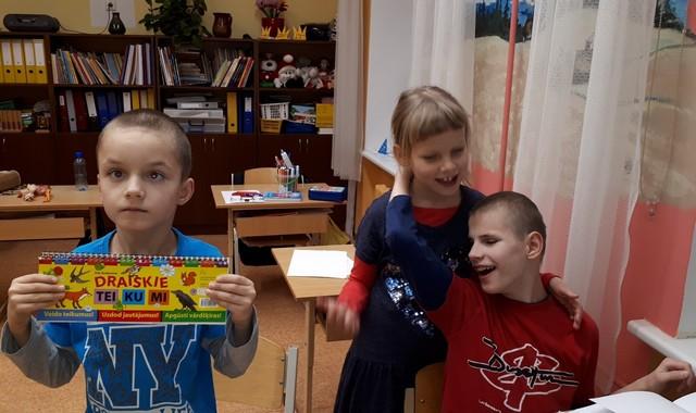 """Zēns rāda grāmatiņu """"Draiskie teikumi"""""""