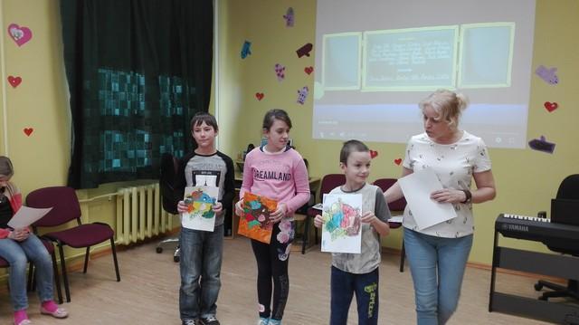 Bērni ar skolotāju Sarmīti Beinaroviču rāda savus darbus