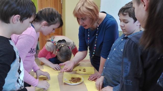 Skolotāja Jolanta Reinvalde ar bērniem pie galda liek burtiņus.