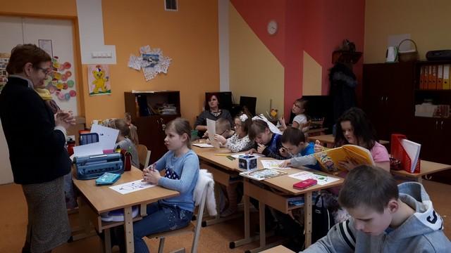Bērni klasē klausās viešņas stāstījumu.