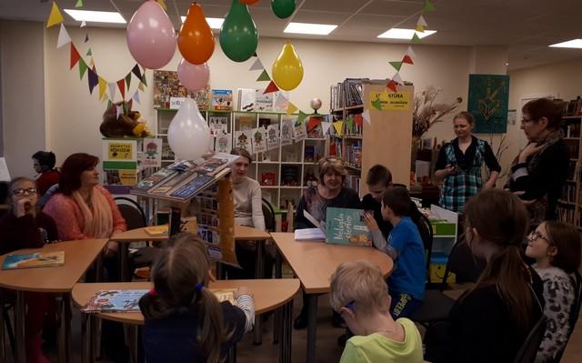 Bērni pie apaļa galda bibliotēkā