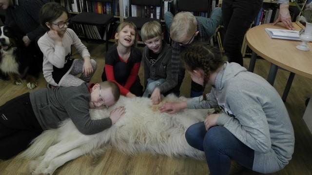 Bērni glauda suni, kurš guļ uz grīdas bibliotēkā.