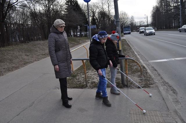 Skolotāja Laimdota Žirba ar skolēniem gatavojas šķērsot Juglas ielu pie luksofora.