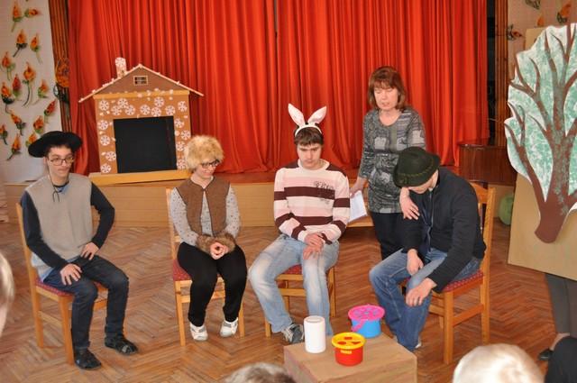 Skolēni ar skolotāju skolas aktu zālē spēlē teātri.