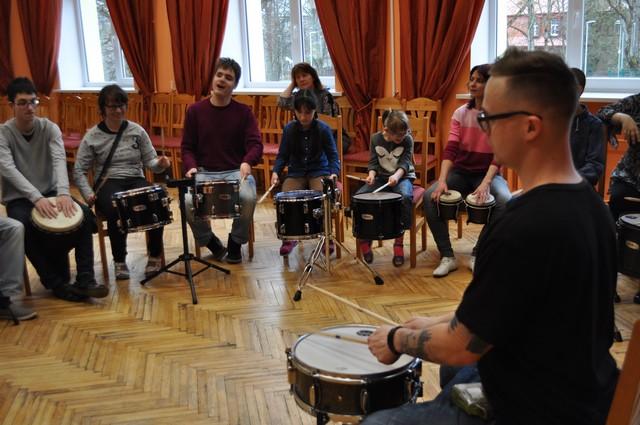 Nodarbību vadītājs centrā, Apkārt bērni spēlē bungas.