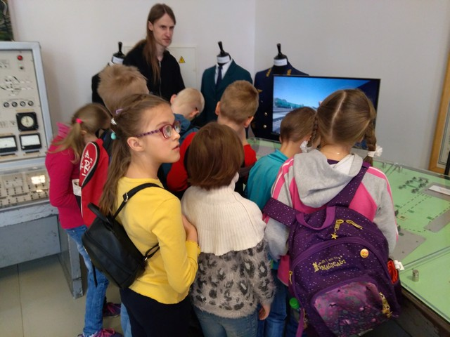 Skolēni muzejā skatās elektroniskās iekārtas