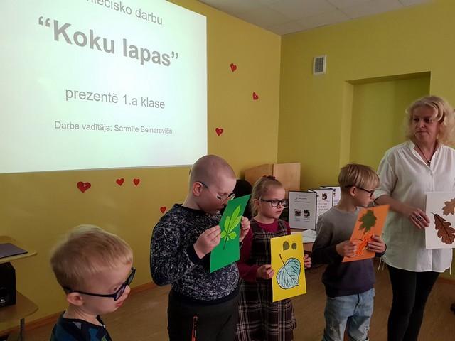 """Skolotāja Sarmīte Beinaroviča ar pirmās klases skolēniem, kas prezentēt darbu """"Koku lapas""""."""