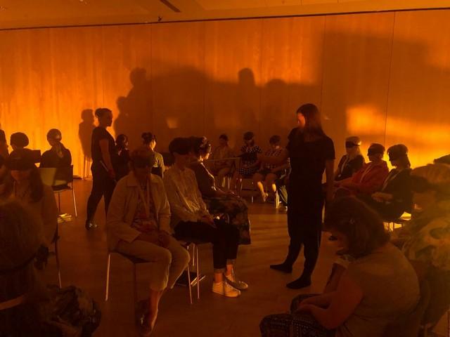 Skolēni sēž tumšā zālē ar aizsietām acīm. Notiek teātra izrāde.