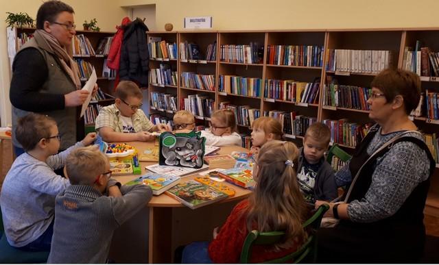 Skolēni un skolotāja Rasma pie apaļa galda klausās bibliotekāres stāstījumu