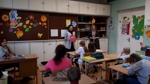 Bibliotēkas darbinieces un skolotāja klases priekšā, bērni sēž solos un klausās viņu stāstījumu
