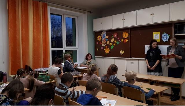 Bibliotēkas darbinieces lasa priekšā fragmentus no grāmatas. Bērni solos klausās.