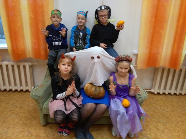 Bērni Helovīna tērpos pozē2. Centrā skolotāja spoka maskā.
