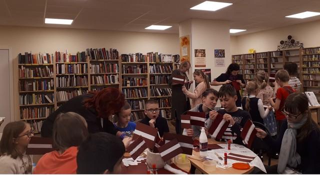Bērni bibliotēkā pie galdiem veidot karodziņus. Skolotājas un bibblitekāres palīdz.